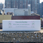 View of Gift Box of Concrete Garden Mind Body Soul Collection, Three Soy Wax 4 oz Candles with NYC Background