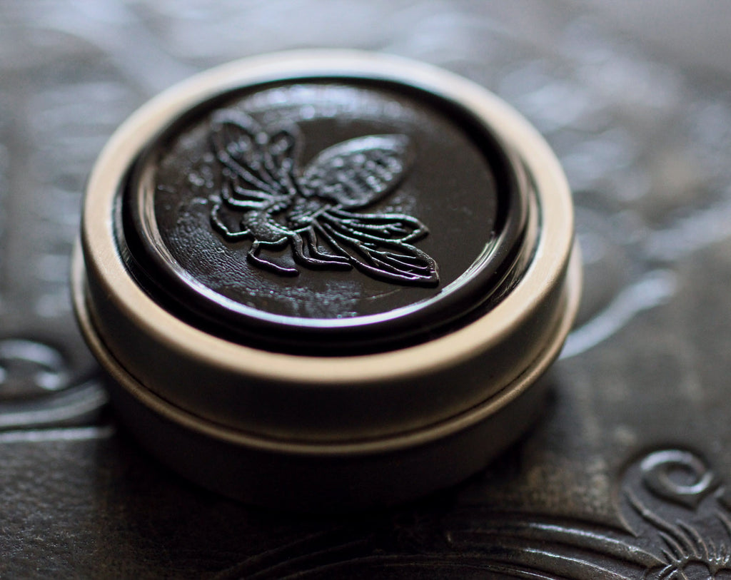 Figure 1: Noir Solid Perfume in Round Tin