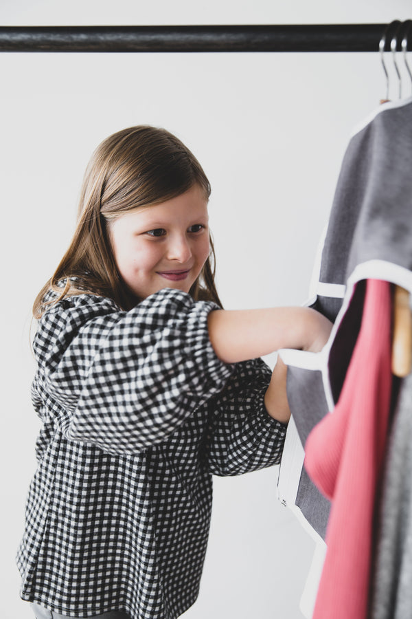 Girl smiling and using The Hanger Valet to organizer her outfit