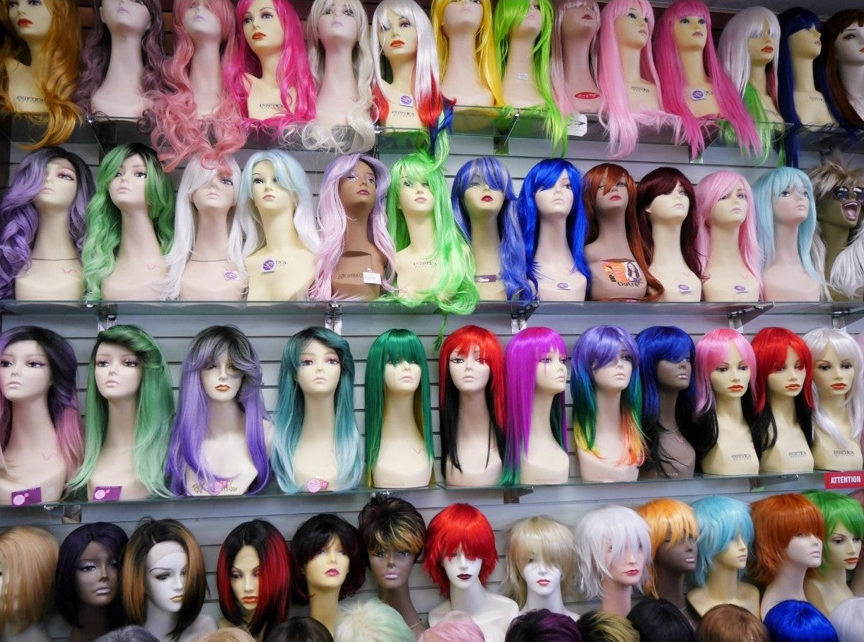 display of many stylish party costume wigs at wig ave