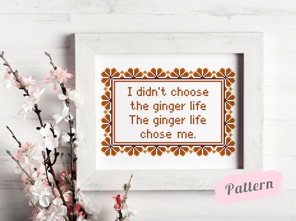 Framed cross stitch reading 'I didn't choose the ginger life The ginger life chose me' surrounded by orange art deco designs. To the left of the frame sits white flowers