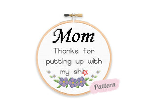Cross stitch reading 'Mom Thanks for putting up with my shit' in black text with blue flowers beneath