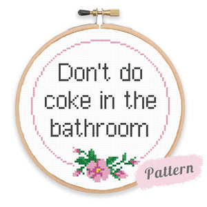 Cross stitch reading 'Don't do coke in the bathroom' in black surrounded by pink circle with pink flowers beneath
