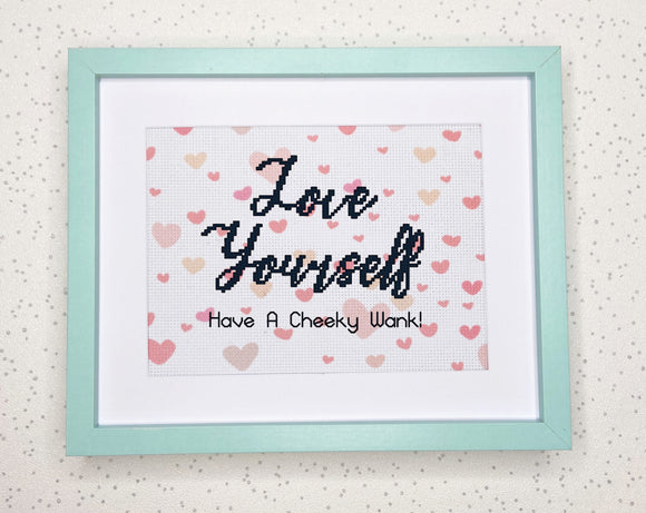 A blue frame surrounds pink heart patterned aida cross stitch fabric with the words 'Love Yourself, Have a cheeky wank!' cross stitched on.