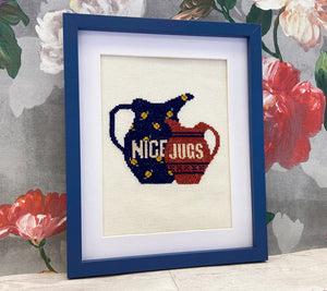 A framed cross stitch of two jugs that reads across one 'NICE' and the other 'JUGS'.