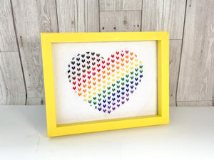 Framed cross stitch of a heart in rainbow colours made up of smaller hearts within