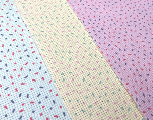Three sheets of aida cross stitch lay flat, each patterned with donut sprinkles: one pastel pink, one mint green and one lemon yellow