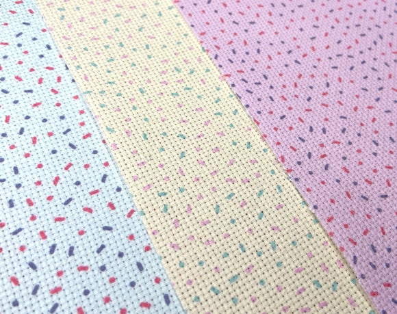 Three sheets of aida cross stitch lay flat, each patterned with donut sprinkles: one  pink, one mint green and one lemon yellow
