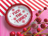 A red bauble with a cross stitched inner reading 'FUCK THE TORIES' sits amongst Christmas decorations and wrapping paper.