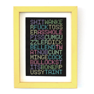 A cross stitch of many different swear words stitched in bright colours on black aida fabricblack frabic