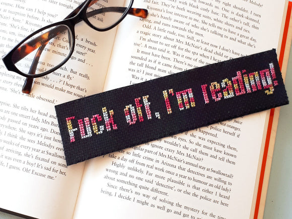 A black fabric bookmark and a pair of glasses lie over an open book. The bookmark is cross stitched with the words 'Fuck off, I'm reading!'
