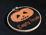 A cross stitch reading 'Empty Inside' in orange text below a hollow orange Halloween pumpkin