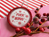 A red bauble with a cross stitched inner reading 'FUCK BORIS' sits amongst Christmas decorations and wrapping paper.