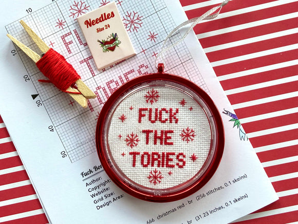 A red bauble with a cross stitched inner reading 'FUCK THE TORIES' sits on a counted cross stitch pattern next to red thread and needles.