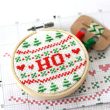 A cross stitch reading 'HO' in red text surrounded by red and green Christmas patterns, sits on a printed cross stitch pattern and next to some thread