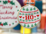 A cross stitch reading 'HO' in red text surrounded by red and green Christmas patterns, hangs in front of other cross stitch hoops