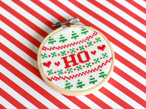 A cross stitch reading 'HO' in red text surrounded by red and green Christmas patterns, sits on a red and white striped background
