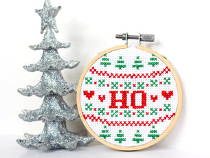 A green and white patterned cross stitch reading 'HO' in large red letters, next to a glittery Christmas tree ornament