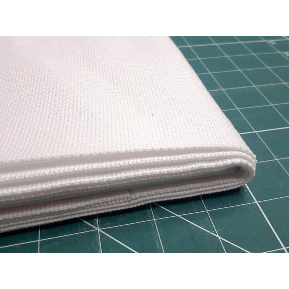 A stack of white aida cross stitch fabric lies on a green measuring board