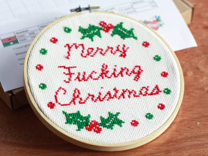 A cross stitch reading 'Merry Fucking Christmas' in red text surrounded by green and red baubles and festive holly leaves