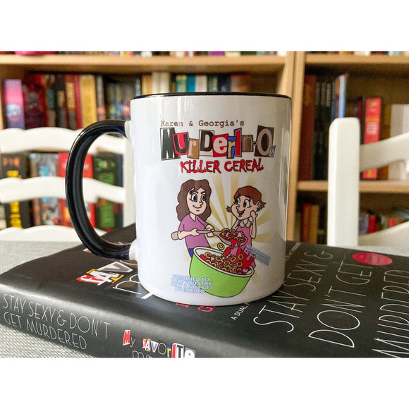 A white mug with black handle sits on a book. The mug reads 'Karen & Georgia's Murderinos Killer Cereal' above a cartoon of two women eating o-shaped cereal from red liquid