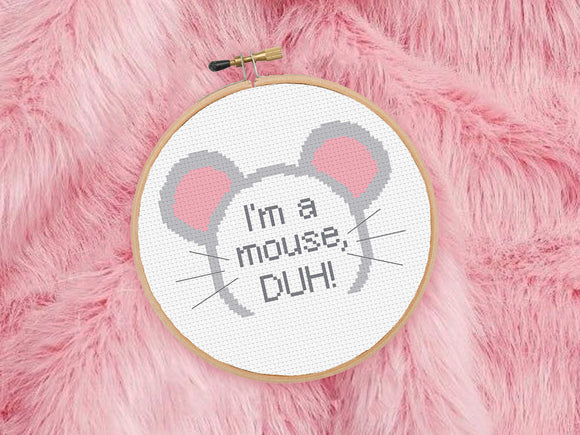 An embroidery hoop lies on pink fur. The cross stitch inside the hoop reads 'I'm a mouse, DUH!' surrounded by toy mouse ears.