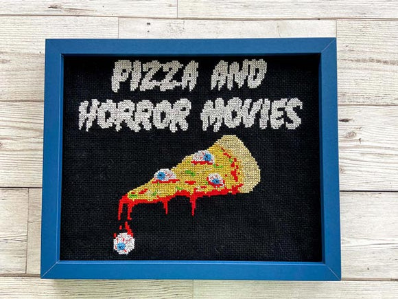 A framed cross stitch of a slice of pizza with eyeballs on as toppings. Above it, white text reads 'pizza and horror movies'.