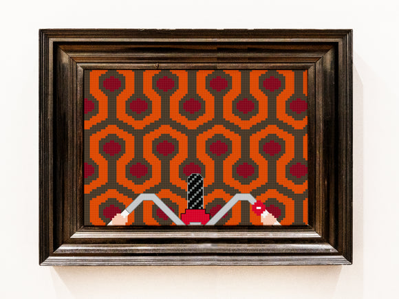 Framed cross stitch of the iconic orange red and grey geometric carpet pattern from the film The Shining. Hands hold onto bike handlebars with a tyre in the middle at the bottom of the design.