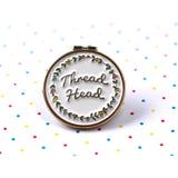 A metal circle reading 'Thread Head' in the centre surrounded by a floral design. Background is white with multi coloured polka dots