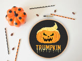 A cross stitch of a pumpkin with blonde quiff. Below it orange text reads 'Trumpkin'. Halloween decorations are placed around the stitch.