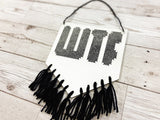 A white banner with 'WTF' cross stitched on in black thread, with black cotton tassels hanging below