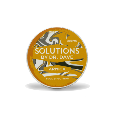A picture of the arnica balm. It is a circular tin with a gold, black and white swirled pattern. The label says 200 milligram Solutions by doctor dave arnica , full spectrum