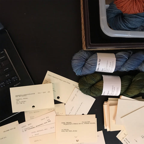 A scattered pile of ex-library catalog cards repurposed as Thank You notes, near a laptop and several skeins of hand dyed yarn.