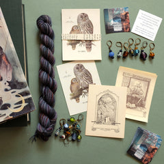 Vintage bookplates, handmade glass bead stitch markers, and a mini skein near a stack of books for the April Spectral Collection featuring Ursula K. Le Guin