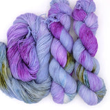 Lilac hand dyed yarn with bright pops of fuchsia, olive green, and cerulean.