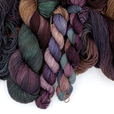 A variegated yarn fades from taupe to eggplant to teal.