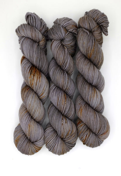 Pewter and charcaol tonal indie dyed yarn speckled with rust speckles.