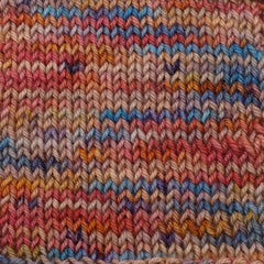 A knit swatch showing a variegated yarn in red and orange with bits of blue and dark purple speckles