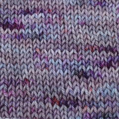 A knit swatch of a lavender and periwinkle yarn with dark purple and bright magenta speckles