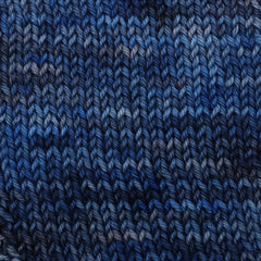 A classic blue and dark gray variegated yarn knit in a stockinette stitch square swatch
