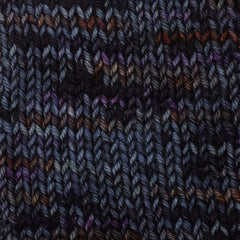 A knit swatch of a midnight blue tonal yarn with dark magenta and rust colored speckles