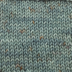 A knit swatch of an aqua green tonal yarn with rust colored speckles