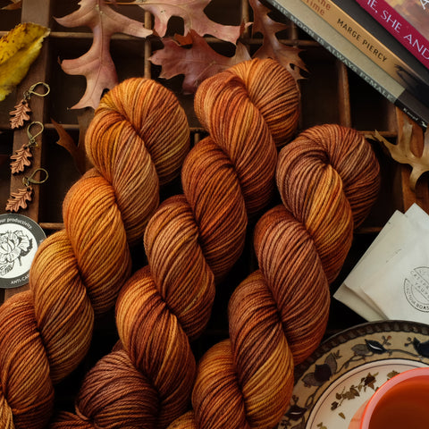Autumnal brown and orange variegated yarn shown with oak leaf stitch markers, tea, a sticker, and books among leaves on a wooden tray.