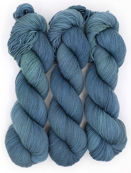 A tonal cerulean and aqua indie dyed yarn inspired by the work of Edward Gorey.