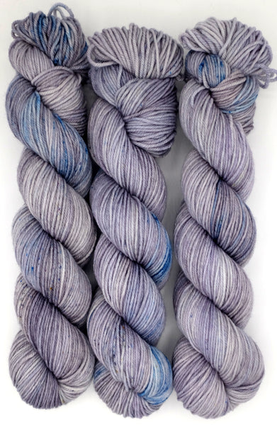 Platinum indie dyed semi-solid yarn scattered with indigo blue speckles.
