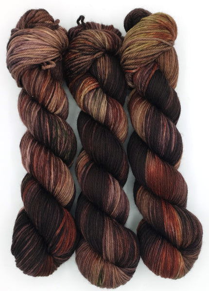 A smoldering ember indie dyed variegated yarn in burnt burgundy and weak yellow flame, inspired by Sappho's fragment 38.