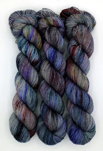 Intricately speckled indie dyed yarn speckled with dramatic jewel tones, inspired by the luscious color palette in Oscar Wilde's novel The Picture of Dorian Gray.