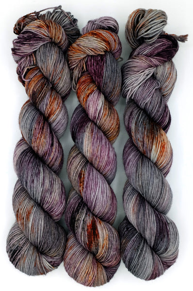 A silver gray indie dyed yarn covered in berry, rust, and black speckles inspired by the Edgar Allan Poe work, The Fall of the House of Usher.
