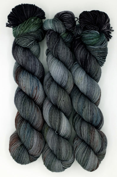 A richly detailed charcoal indie dyed yarn with eggplant and forest accents, speckled with classic blue, chartreuse, and brick red.