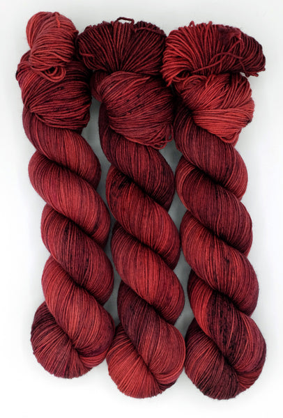 A dramatic wind and blood red indie dyed tonal yarn with kohl black and berry speckles, inspired by Bram Stoker's character, Mina.